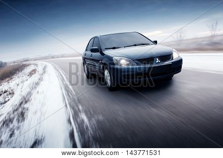 Saratov, Russia - November 30, 2014: Car Mitsubishi Lancer drive on asphalt countryside road at winter daytime