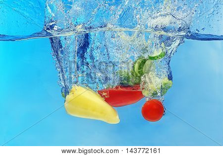 Vegetables falling into water on color background