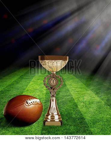 American football and trophy cup on green field with spotlights
