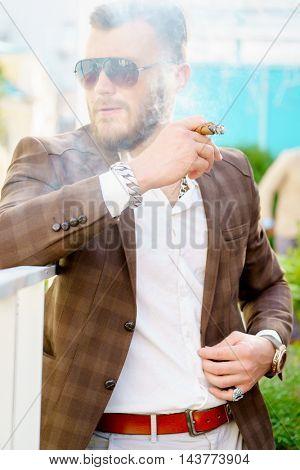 Casual man in elegant suit smoking cigar