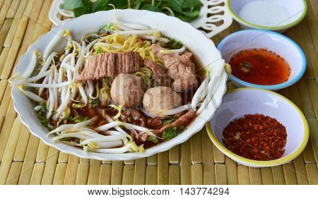 Chinese noodle with pork ball in brown soup and seasoning cup