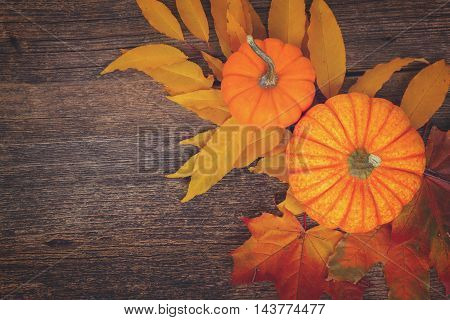 orange with fall red and yellow leaves on wooden textured table, top view, retro toned