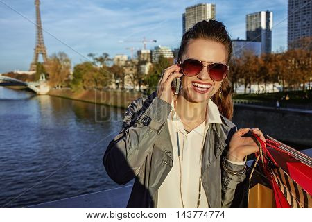 Woman With Shopping Bags Talking On Cell Phone Near Eiffel Tower