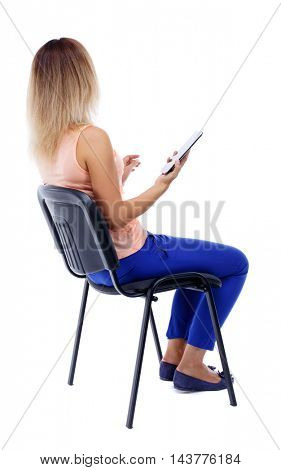 back view of woman sitting on chair and looks at the screen of tablet.  Rear view people collection.  backside view of person.  Isolated over white background. The blonde in a pink vest sits on a