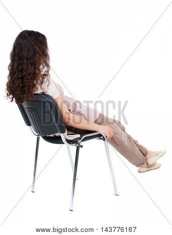 back view of young beautiful  woman sitting on chair.  girl  watching. Rear view people collection.  backside view of person.  Isolated over white background. Long-haired curly girl sitting on a chair