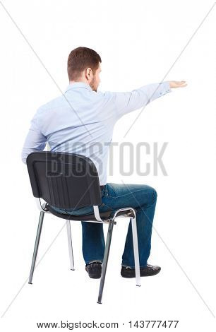 back view of young business man sitting on chair and pointing. Rear view people collection. Bearded businessman sitting on a chair and shows his hand forward.