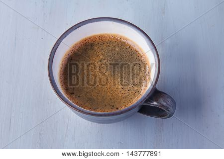 Blue Mug Of Hot Coffee. Light Wood Background. Top View
