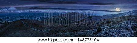 panoramic summer landscape under blue sky with clouds. Path through hillside meadow on Borzhava mountain ridge in Carpathians at night in full moon light