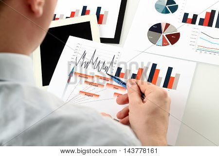 Close-up image Of Businessman Analyzing Graphs with touchpad
