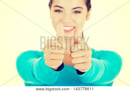 Teen woman gesturing thumbs up