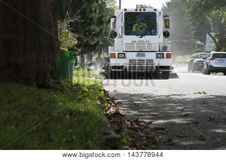 Village Road, York, Pennsylvania, USA - August, 7, 2016 - City street sweeper sweeping cleaning the road