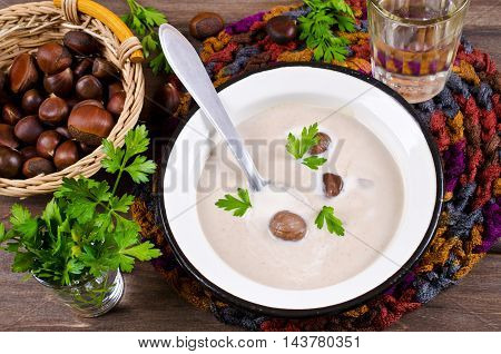 Cream soup of pureed chestnuts on a wooden background. Selective focus.