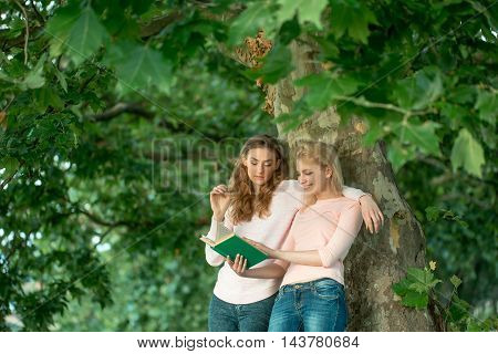 Two young girls best friends read book under green tree in summer park