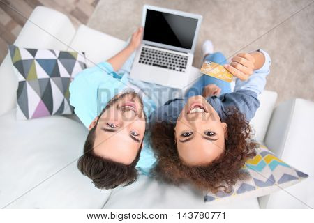 Young man and woman using credit card and laptop for online shopping