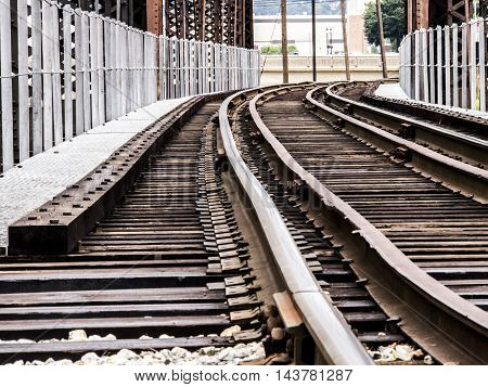 Train tracks going over a bridge that is old and rsty