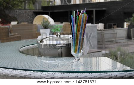 Cocktail tubes in clear glass on table at the hotel courtyard