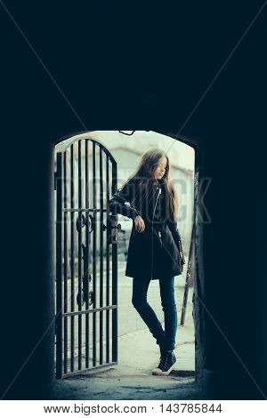 Young teen girl in fashionable coat standing near forged door in arch