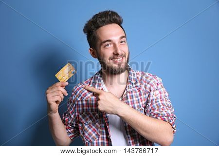 Young man holding credit card on blue background
