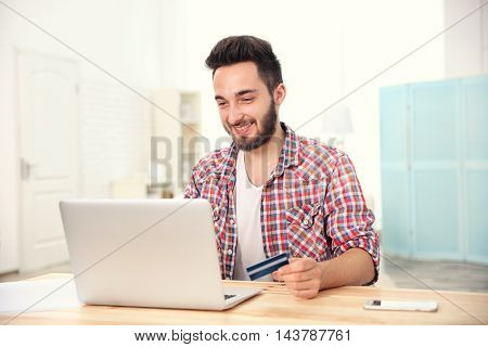 Man using credit card and laptop for online shopping