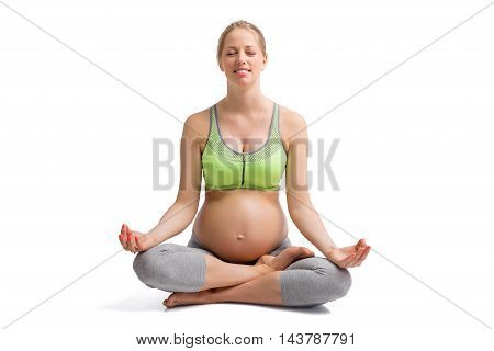 Pregnant woman sitting in lotus position and meditating