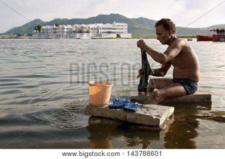 UDAIPUR, RAJASTHAN, INDIA - Jul 23 2010: Man washing clothes in Lake Udaipur