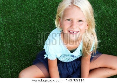 beautiful blonde smiling girl sitting on the grass on a summer day