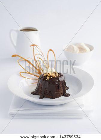 Chocolate lava cake, ice cream and a jug of chocolate sauce.