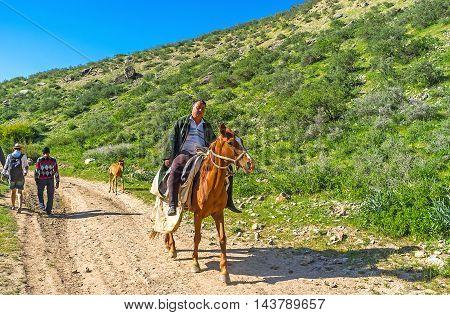 ZARMAS UZBEKISTAN - MAY 2 2015: The horseman falls asleep during slowly riding along the Zarmas gorge in Gissar Nature Reserve on May 2 in Zarmas.
