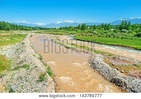 The Yakabag Darya River flows among the meadows and forests with the snowbound Gissar Range of Pamir-Alay mountains on the background Uzbekistan.