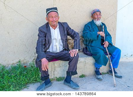 SAMAK UZBEKISTAN - MAY 2 2015: The senior Uzbek and his elderly son sit next to their house and watch the passers on May 2 in Samak.