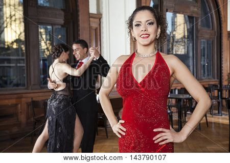 Woman With Hands On Hip Standing While Dancers Doing Tango