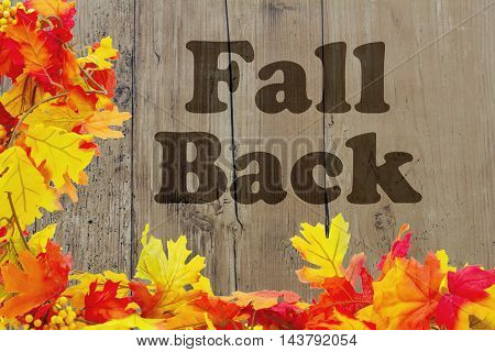 Fall Back Time Change Autumn Leaves with grunge wood and words Fall Back