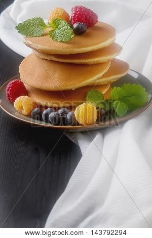 English fresh homemade pancakes with raspberries, blueberries, mint. On a gray plate. Black wood background