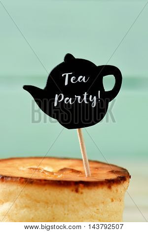 closeup of a cheesecake topped with a black teapot-shaped signboard with the text tea party written in it, against a blue background