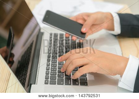 Closeup of business woman hand touch phone over laptop keyboard