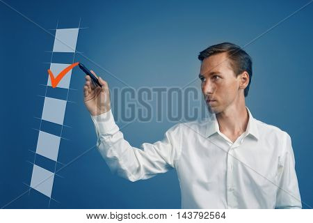 Young business man in white shirt checking on checklist box. Blue background.