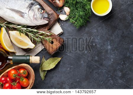 Raw fish cooking and ingredients. White wine, dorado, lemon, herbs and spices. Top view with copy space on stone table