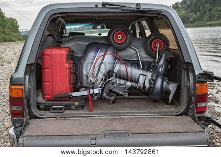 pvc boat with outboard engine is packed in the car trunk