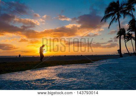 Honolulu, Hawaii, USA - Dec 21, 2015: Setting sun over beach at Ala Moana Park, along Ala Moana Park Drive. The beach overlooks Mamala Bay. A person walks in front of the setting sun.