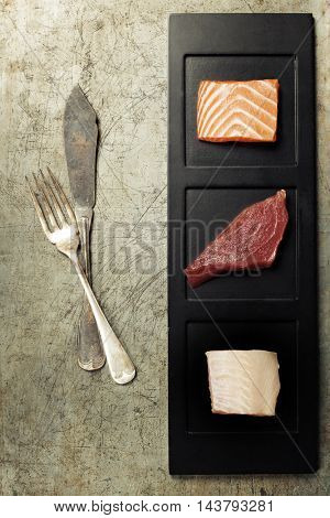 Assortment of raw fish on rustic background.
