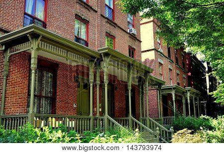 New York City - August 24 2009: Brick homes with wooden Victorian porches and gardens line Astor Row on West 130th Street in Harlem