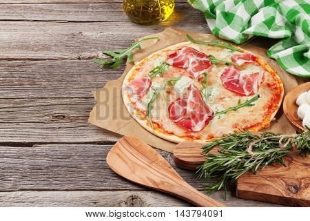 Pizza with prosciutto and mozzarella on wooden table. View with copy space