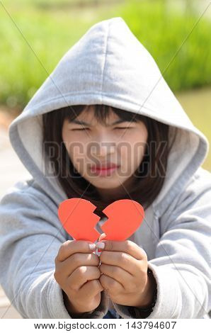 Young girl holding broken paper red valentine heart