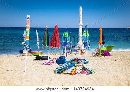 Chairs and umbrella on the beautiful tropical beach, as a sign of vacation. Greece.