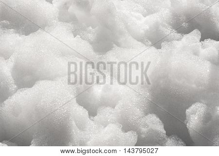 Close up detail of thick white soapy foam bubbles in a full frame background texture
