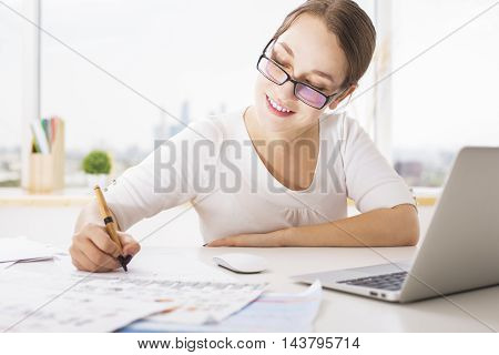 Young smiling businesswoman doing paperwork at modern bright workplace with laptop computer