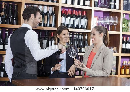 Bartender Serving Red Wine To Female Customers