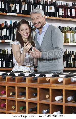 Portrait Of Couple With Wine Bottles Standing At Rack