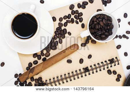 Close up and top view of spiral notepad coffee cup beans and cigar on white desktop