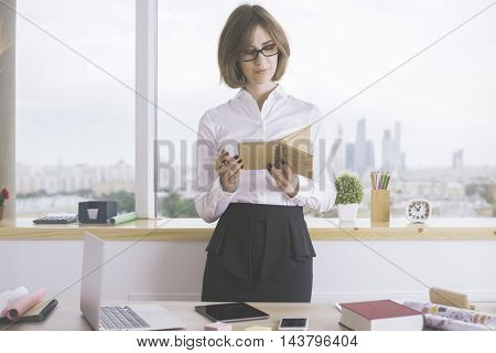 Portrait of classy young business woman with notepad in hands standing at office table with various electronic devices and other items